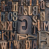 Wooden printers typeface letters. Jumbled arrangement of different sized wooden printers typeface letters of the alphabet forming a background pattern Stock Image