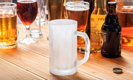 A wooden pub counter, focus on an empty frosty mug of beer. An empty frosty mug of beer on a wooden pub counter Stock Image