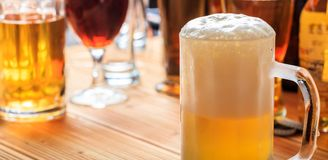 A wooden pub counter, focus on a full frosty mug of beer. A full frosty mug of beer on a wooden pub counter Royalty Free Stock Photo