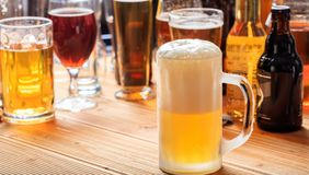 A wooden pub counter, focus on a full frosty mug of beer. A full frosty mug of beer on a wooden pub counter Royalty Free Stock Photography