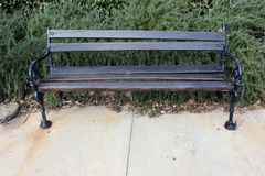 Wooden public bench with black wrought-iron sides Royalty Free Stock Photo