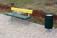Wooden public bench with same style trash can Royalty Free Stock Images