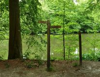 Wooden Public Footpath Sign by a forest lake. A wooden public footpath sign on a forest path by a lake on an overcast day Royalty Free Stock Photos