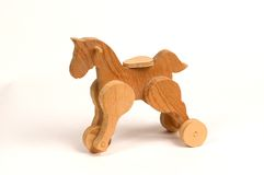 Wooden pull toy. For children, a horse on wheels with a saddle royalty free stock photo