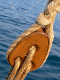 Wooden pulley block. Pulley block on an old wooden sail boat with ropes (rigging element Stock Photo
