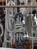 Wooden pulleys and ropes on vintage sailing boat. Details of wooden pulleys block and ropes on an ancient sailing boat. Vertical view with coastline background stock photo