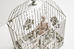 Wooden puppet in bird cage sitting sad Royalty Free Stock Image