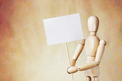 Wooden puppet holding blank white poster in its hands Stock Image