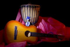 Wooden puppet of a little cheerful boy with a guitar and a drum. Wooden puppet of a little cheerful boy with a guitar and an African drum Royalty Free Stock Images