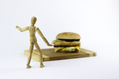 Wooden puppet looking at a hamburger. A wooden puppet looking at a hambuger on a white background Royalty Free Stock Photos