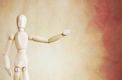 Wooden puppet points aside with its hand. Conceptual image Stock Image