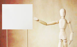 Wooden puppet points to blank white broadsheet with its hand. Conceptual image about presentation Stock Photo