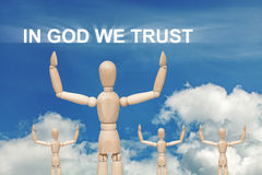 Wooden puppet on sky with words IN GOD WE TRUST Royalty Free Stock Image