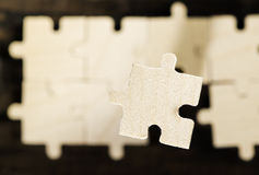 Wooden puzzle on dark background. Royalty Free Stock Photo