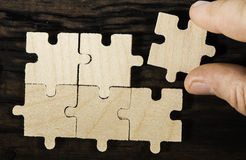 Wooden puzzle on dark background. Royalty Free Stock Images