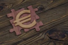 Wooden puzzle Euro sign on wood background. Symbol of european money. business, finance background Royalty Free Stock Images