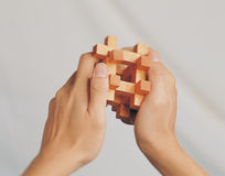 A wooden puzzle in a man's hands Stock Image