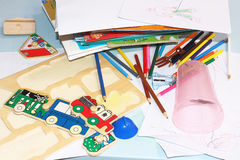 Wooden puzzles, colored pencils and books are scattered on the children`s table. royalty free stock photography