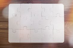 Puzzles on a wooden background. Royalty Free Stock Photo