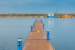 Wooden quay in Constanta touristic harbor over blue sky and two ships Royalty Free Stock Images