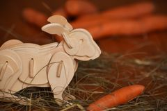 Wooden rabbit or bunny with carrot in hay royalty free stock photos