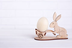 A wooden rabbit with an egg. Easter decoration on wall background. Joyful spring holiday royalty free stock images