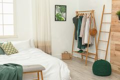 Wooden rack with clothes in bedroom interior royalty free stock image