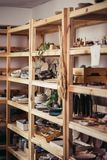 Many different pottery standing on the shelves in a potery workshop. Wooden racks in a pottery workshop in which there are pottery, many different pottery Royalty Free Stock Photos