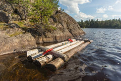 Wooden raft at the rocky shore Royalty Free Stock Image