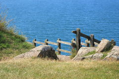 Wooden railing with path down to the blue ocean Royalty Free Stock Photo