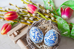 Wooden ratchet instrument with painted blue eggs in wicker nest with pussycats and tulips flower. Royalty Free Stock Photography