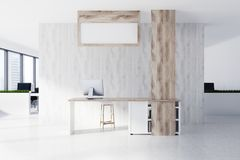 Wooden reception, posters. Wooden reception desk standing on a concrete floor of a modern office with white and dark wooden walls. A poster is hanging above the Stock Photo