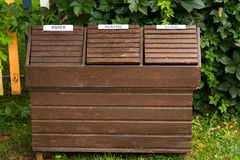 Wooden recycle bins in a park. Sort to glass, paper and plastic. Ecology concept.  Royalty Free Stock Image