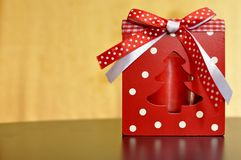 Wooden red box with a candle inside and white and red ribbon for Christmas decoration. royalty free stock photos