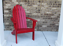 A wooden red chair on a front porch. By a brick wall Royalty Free Stock Photography