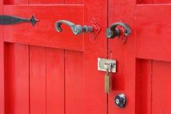 Wooden red door with handle. Closeup of old wooden red door with metal handle Stock Image