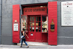 Wooden red doors and a woman walking. Wooden double doors at the le Coq Gourmand restaurant and a woman walking with bag and short hair in Marseille, France Royalty Free Stock Images