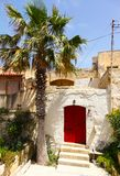 Wooden red front door to the house. Red wooden front door to the house in the Mediterranean and palm Stock Photography