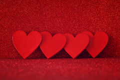 Wooden red hearts on red shiny background Royalty Free Stock Photo