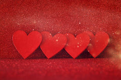 Wooden red hearts on red shiny background Stock Photo