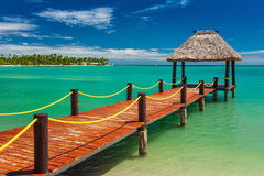 Wooden red jetty extending to tropical green lagoon, Fiji. Islands Royalty Free Stock Photo