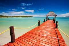 Wooden red jetty extending to tropical lagoon. Wooden red jetty extending to tropical green lagoon Royalty Free Stock Image