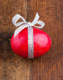 Red painted egg. Wooden red painted egg with bow and ribbon on old wooden background Stock Photos