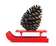 Wooden red sled with brown pine cone Royalty Free Stock Images