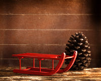 Wooden red sled with brown pine cone Stock Photos