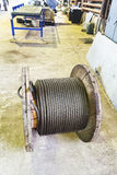 Wooden reel with steel rope in mechanical shop Stock Photos