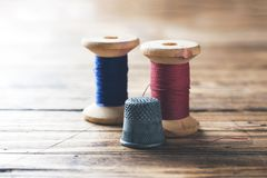 Wooden reel with thread and fingertip close-up. Selective focus. Rendered image.  royalty free stock images