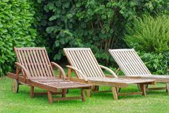 Wooden Relax Lounger in a garden. Three wooden relax loungers on a green lawn with a hedge in the background stock image