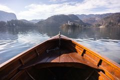 Wooden rent boat on a Bled lake, end of the boat facing towards Lake Bled island with copy space- famous tourist stock images