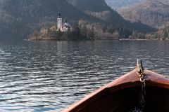 Wooden rent boat, end of the boat facing towards Lake Bled island, focus on Bled island - famous tourist destination in royalty free stock photo
